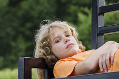 Relaxing. Bored teen laying across a park bench Stock Image