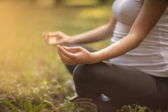 Relaxing the both of them. Pregnant woman having meditation in nature. Copy space. Close up. Focus is on hand stock photo