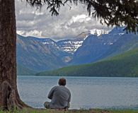 Relaxing at Bowman Lake. This image of the man relaxing on the shore of Bowman Lake was taken in Glacier National Park in western Montana Stock Photography