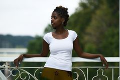 Relaxing on the bridge. African American woman stands and relaxes on a bridge royalty free stock photography