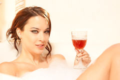 Relaxing in a bubble bath. Attractive woman drinking a glass of wine in the bath lots of room for copy copyspace Stock Photo