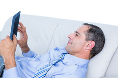 Relaxing businessman on a sofa with a tablet Royalty Free Stock Photography