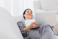 Relaxing businesswoman lying on sofa using laptop Royalty Free Stock Image