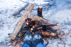 Relaxing by the campfire in winter - woman in hiking boots warmi Royalty Free Stock Photo