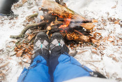 Relaxing by the campfire in winter - woman in hiking boots warmi Stock Image