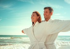 Carefree couple. Relaxing carefree beach couple outstretched arms royalty free stock photography