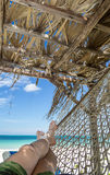 Relaxing by the caribbean ocean at cuban beach. Resting under a palapa in a hammock on a sunny day at the beach Royalty Free Stock Photo