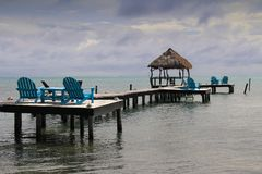 Relaxing Caribbean view from bright blue wooden loungers. Relaxing Caribbean view from bright blue wooden loungers on dock stretching into the sea with a palapa Royalty Free Stock Photography