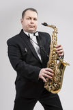 Relaxing Caucasian Man Posing With Saxophone Against White Background Stock Image