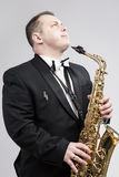Relaxing Caucasian Man Posing With Saxophone Against White Background Royalty Free Stock Image