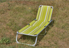 Relaxing chair ready to use on grass. Meadow closeup royalty free stock photography