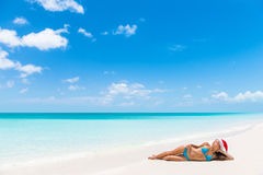 Relaxing christmas beach vacation woman sunbathing. Relaxing christmas vacation woman lying down on perfect white sand sunbathing. Santa hat woman relaxing on stock image