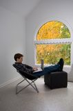 Relaxing with a computer. Teen male working with a notebook computer with fall foliage visible through a large window Stock Photos