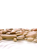 Relaxing concept. Warm pebbles and water ripples isolated over white background Royalty Free Stock Photography