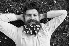 Relaxing concept. Hipster on happy face lays on grass, top view. Man with beard and mustache enjoys spring, green meadow. Background. Guy looks nicely with stock photography