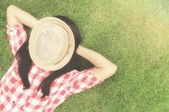 Relaxing concept. Trendy hipster asian woman relaxing on the green grass with hat on her face. Relaxing concept. Vintage tone Retro filter effect,soft focus,low Stock Photos