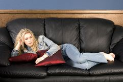Relaxing on Couch. Beautiful blond model relaxing on black leather couch/sofa Stock Image