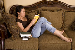 Relaxing on couch reading Stock Image