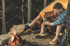 relaxing couple on hiking trip drinking beer together while sitting royalty free stock image