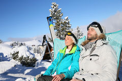 Relaxing couple on the slopes taking sun Royalty Free Stock Images