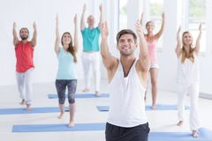 Relaxing in crescent lunge pose. Group of yogins relaxing in a crescent lunge pose, stretching their arms stock photography
