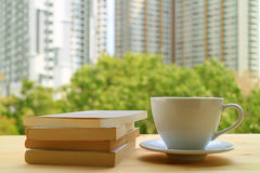 Relaxing with a cup of hot drink and some books by the window, with Blurred Background. Of green trees and high buildings Stock Image