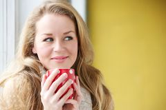 Relaxing with a cup of tea. Close up portrait of a young woman relaxing with a cup of tea at home royalty free stock photography
