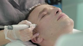 Relaxing dark-haired man during the hydrofacial vacuum care procedure slow motion