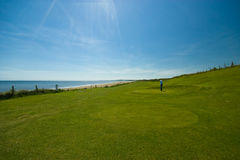 Relaxing day. A man play golf near the sea Stock Image
