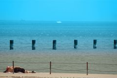A relaxing Day on the Beach. A man relaxing on a beautiful beach with ships in the background stock photo