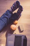 Relaxing day at work. Girl siting on the floor with laptop, fruits and business cards Royalty Free Stock Image