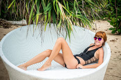 Relaxing on the deck chair. Beautiful young women in sunglasses relaxing on the deck chair on the beach. Sexy woman. Relaxing on the deck chair. Beautiful young Royalty Free Stock Images
