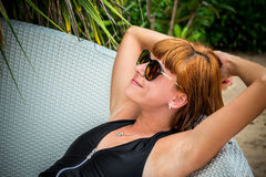 Relaxing on the deck chair. Beautiful young women in sunglasses relaxing on the deck chair on the beach. Sexy woman. Relaxing on the deck chair. Beautiful young Stock Images
