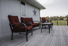 Relaxing on the deck. Red patio chairs on the deck Stock Images