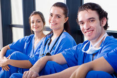 Relaxing docotrs. Group of young doctors relaxing in hospital hallway during break stock image