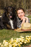 Relaxing with a dog. Woman lying with her ​​dog relaxing in a garden Stock Images