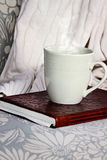Relaxing Drink. A hot relaxing cup of coffee or cocoa with a book sitting on a comfortable chair with blanket. Extreme shallow depth of field stock image