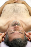 Relaxing Ears. Mature male receiving ear reflexology massage of both ears at the same time royalty free stock images