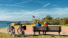 Relaxing elderly couple on their bike trip to Hook of Holland. Relaxing elderly couple on their bike trip. They are watching the incoming ships at the harbour of stock photo