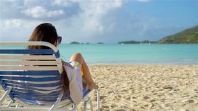 Relaxing and enjoying on summer vacation, woman lying in sunbed on beach. SLOW MOTION. Relaxing and enjoying on summer vacation, woman lying in sunbed on beach stock footage