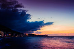 Relaxing Epic Island Sunset By The Sea. Relaxing, beautiful, epic island sunset scenery in a windy day of fall season with ocean surface and dark blue clouds Royalty Free Stock Photography