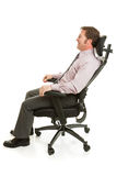 Relaxing in Ergonomic Chair. Businessman relaxing in a comfortable ergonomic office chair. Full body isolated on white royalty free stock image