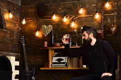 Relaxing evening. Man with beard holds glass of mulled wine hot seasonal beverage. Guy in cozy warm atmosphere drinking Stock Image