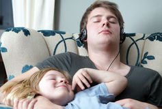 Relaxing family sleeping brothers. Sleeping in chair at home. brothers resting, one teenager with headphones and child with long blond hair. family relaxing Stock Images
