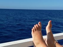 Relaxing Feet. On the railing of a boat at sea Royalty Free Stock Images