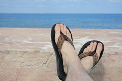 Relaxing Feet. Feet in sandals propped up on a wall with an ocean view on vacation Stock Photography