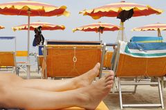 Relaxing feet on a beach holiday. Woman`s or men feet on the coarse sand near the sea. Relaxation at sea in countries with cold climates. Beach vacation holidays stock photo