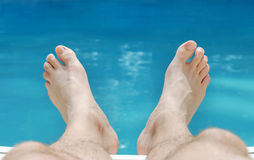 Relaxing Feet in Summer. Two feet relaxing in sunlight with swimming pool water in the background Stock Photography