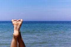 Relaxing feets. The feets of a relaxing girl lying at the beach Stock Image