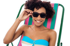 Relaxing female model adjusting her shades Stock Photos